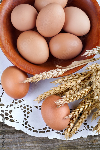 Eggs in wooden bowl with spikes of wheat