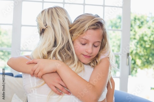 Girl with eyes closed hugging mother
