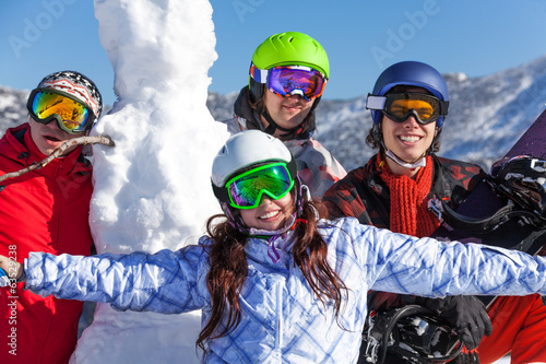 Snowboarders and snowman wearing goggles