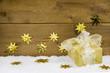 Goldenes Geschenk auf Holz - weihnachtlicher Hintergrund