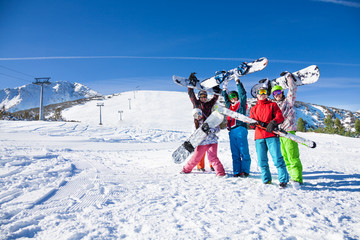 Five friends holding snowboards and skies together