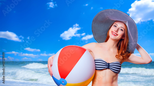 Redhead girl with toy ball on the beach