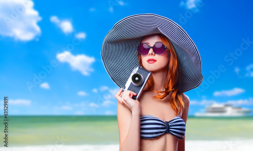 Redhead girl with retro camera on the beach