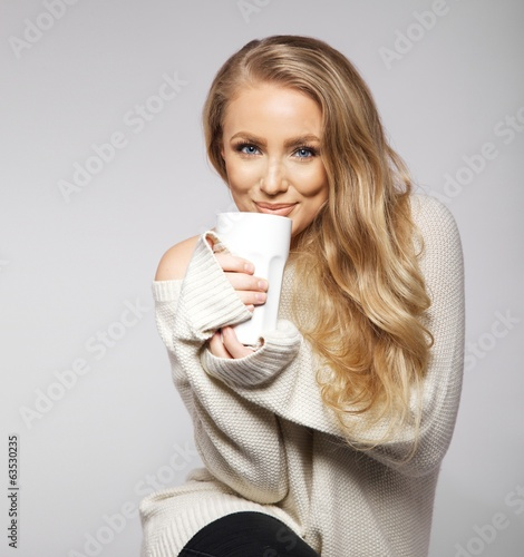 Cute smiling girl in oversized sweater holding cup.