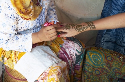 Hand being decorated with henna India