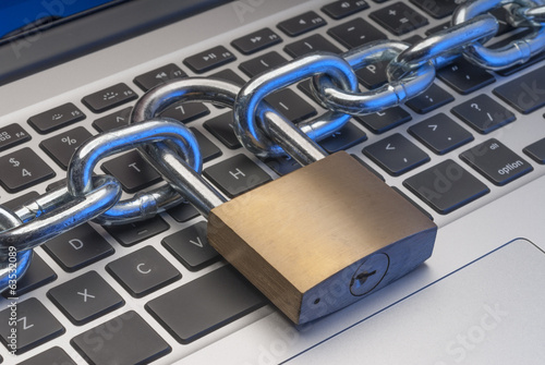 Padlock and chain on keyboard to illustrate internet security