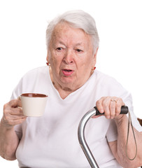 Old woman holding coffee or tea cup