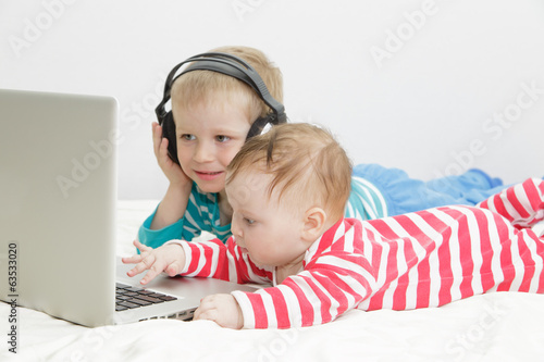 little girl with brother looking at laptop