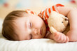 infant baby sleeping with plush toy - 63533480
