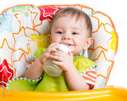 smiling baby drinking from bottle sitting in high chair