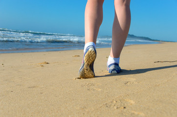 Woman runner legs in shoes on beach, running concept
