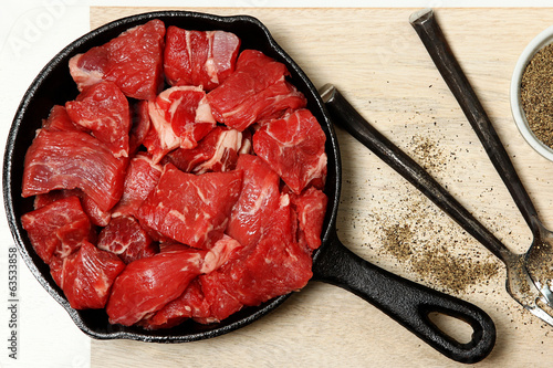 Raw Cubed Beef in Cast Iron Skillet on Table