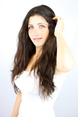 Shy girl looking in studio touching her long hair