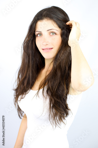 Shy girl looking in studio touching her long hair