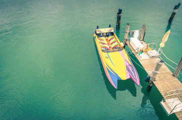 Multicolored speedboat ready to sail at wooden pier - Retro nost