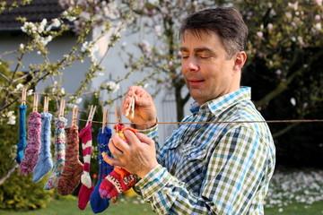 bunte Socken im Garten auf Wäscheleine gehängt