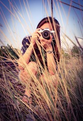 Pretty photographer is shooting the grassland