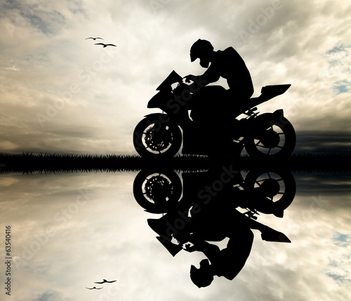 Man motorcyclist at sunset