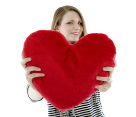 Beautyful young woman smiling with heart shaped pillow