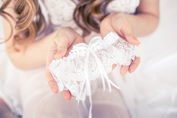 The bride holds the garter in the Studio.