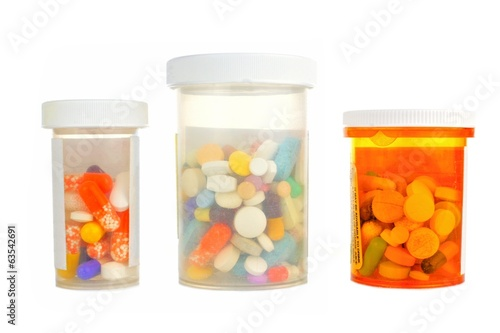 Three pill bottles filled with assorted medications