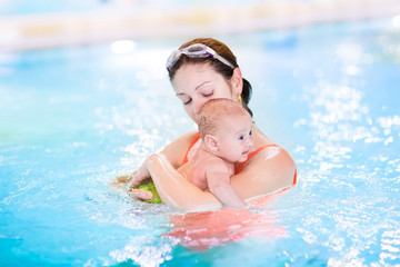 Young mother and her newborn baby son in a swimming pool