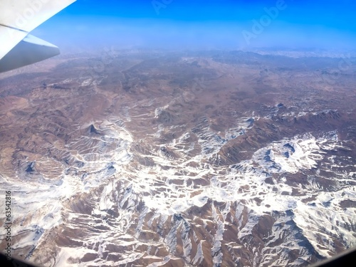 snow mountain tops undre a plane wing