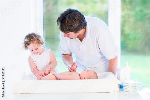 Adorable toddler girl helping her father to change a diaper
