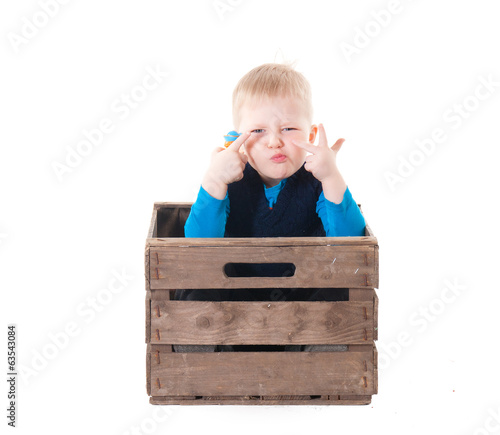 Little boy in wooden box
