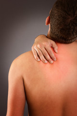 Young male eith neck pain against