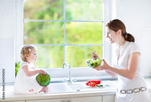 Young mother and her cute toddler daughter cooking together