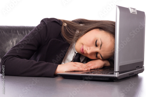 Overworked businesswoman sleeping on her laptop being exhausted