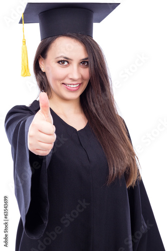 Happy young woman wearing cap and gown with thumb up