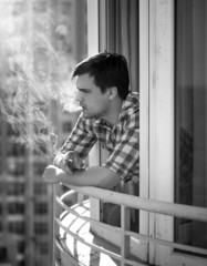Monochrome portrait of depressed man smoking