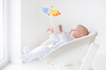 Cute newborn baby boy watching a colorful mobile toy
