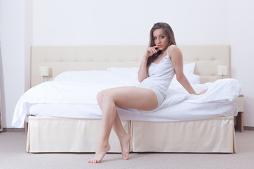 Image of curvy young girl sitting on hotel bed