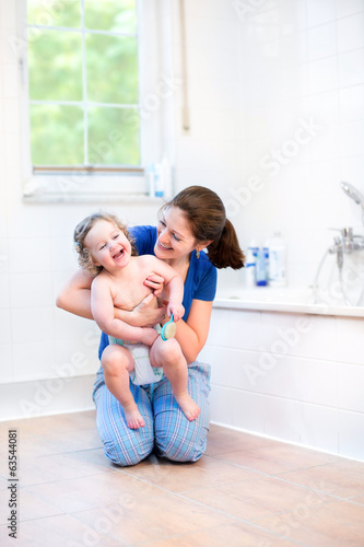Young mother and her happy baby playing together in a bathroom