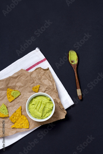 Nacho Chips and Guacamole on dark background