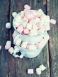marshmallows in metallic cups on wooden table