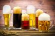 Leinwanddruck Bild - Variety of beer glasses on a wooden table
