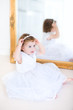 Adorable curly toddler girl trying on a beautiful white dress