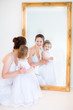 Young mother and her adorable toddler daughter in a white dress