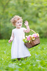 Funny toddler girl playing with a flower basket on Easter mornin