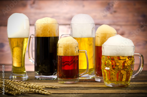Poster Variety of beer glasses on a wooden table