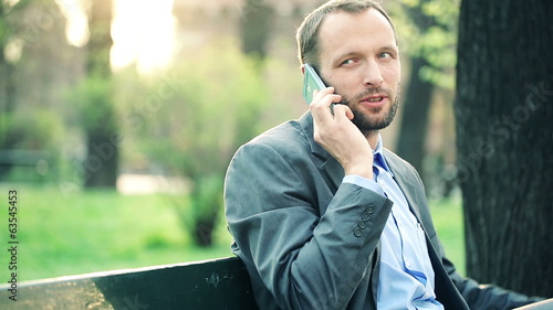 Young businessman talking on cellphone in city park