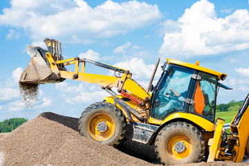 Excavator machine unloading gravel during earth moving works