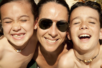 Madre con hijos en primer plano bajo el sol