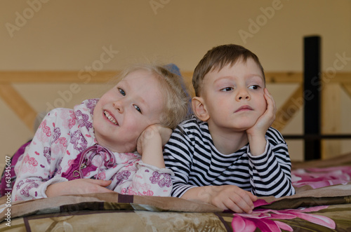 Young brother and sister lying on a bed together