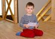 Little boy kneeling on the floor reading