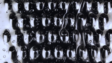Water drips and flows down on a metal grater. Macro.